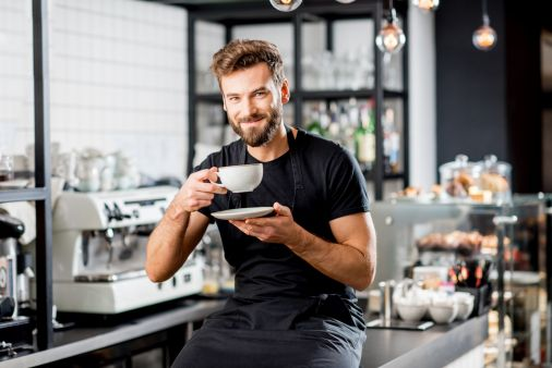 Portrait of a handsome barista sitting with coffee at the bar of the modern cafe interior